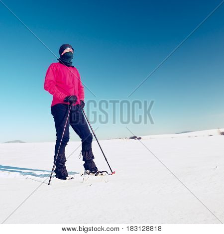 Winter Tourist With Snowshoes Walk In Snowy Drift. Hiker In Pink Sports Jacket
