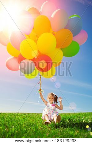 Balloons for the birthday against the background of the sky and green grass. Summer fun party. Summertime holiday.