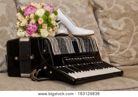 Bridal bouquet shoes and rings on accordion.