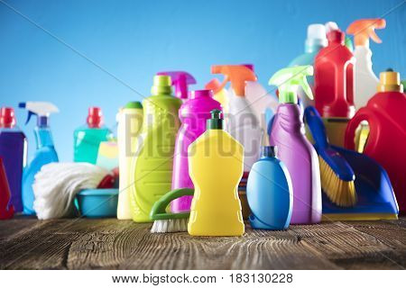 Spring cleanup theme. Variety of colorful house cleaning products on a rustic wooden table and blue background.