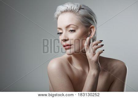 Sensual young woman with short hair and black nails.
