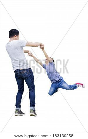 Image of young father is spinning his son in the studio isolated on white background