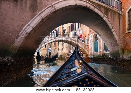 VENICE, ITALY - 09.04.2017: View from gondola under old bridge in street of Venice Italy