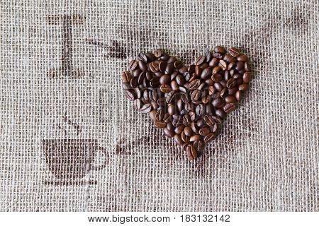 I love coffee. Burlap texture with coffee beans heart shape background, love symbol with cup and arrows. Sack cloth canvas and seeds at hessian textile