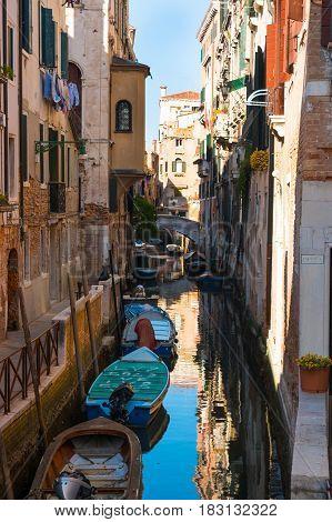 VENICE, ITALY - 09.04.2017: Narrow street with a canal bridge boats in Venice Italy