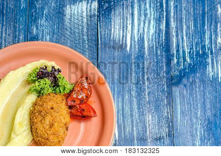 Mashed potatoes chicken tomatoes and herbs on a red plate stand on a blue denim background