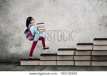Picture of a little school girl carrying a pile of book while walking on the stair made of book. Back to School concept