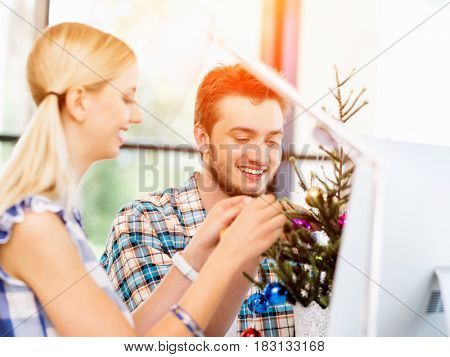 Young man decorating christmas tree in office