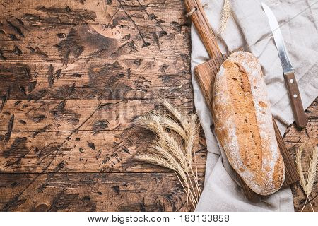 Fresh rye bread on a cutting board over wooden table. Top view