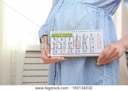 Young pregnant woman holding calendar near belly at home
