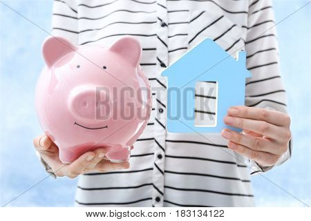 Savings concept. Woman holding piggy bank and house figure on light background