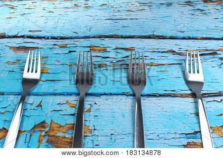Four forks on blue wooden background/ These are forks on blue old planks.