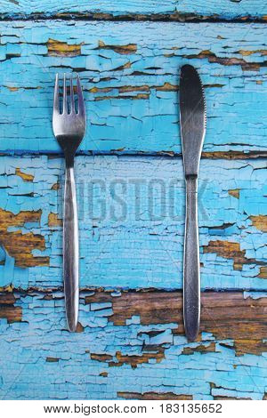 These are cutlery on blue wooden background