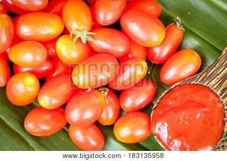 ketchup in spoon with tomatoes put on green leaf