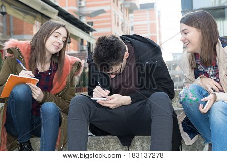Three happy smiling students take notes on the campus