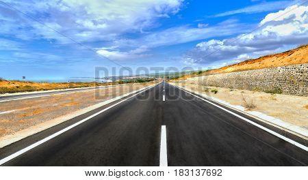 Long highway crossing sunny desert wind under dramatic sky summer day
