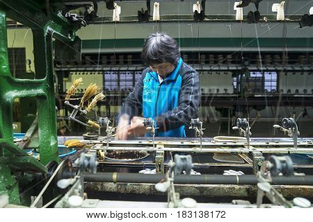 SUZHOU China. April 18 2017: Chinese woman working with spinning machine of silkworm cocoons in Suzhou China