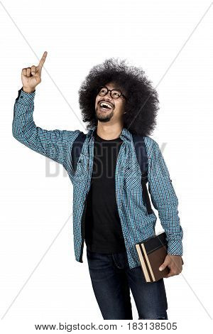 Young afro man getting inspiration while pointing at copy space and holding book isolated on white background