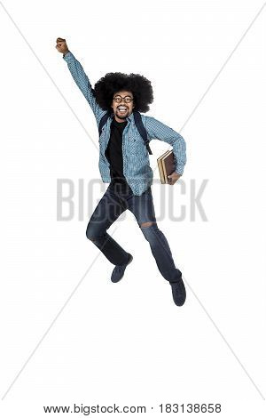 Young male student jumping in studio while holding book in his hand isolated on white background