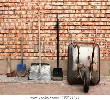 Old garden tools and by standing at a brick wall