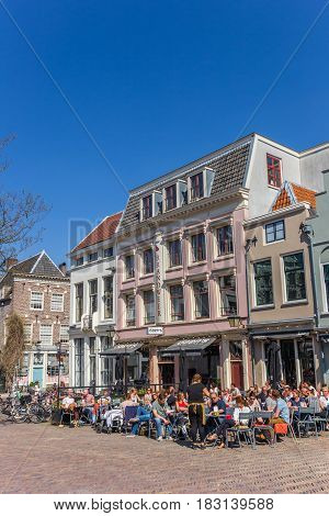 UTRECHT, NETHERLANDS - APRIL 09, 2017: People sitting and drinking ouside a cafe in Utrecht, Holland