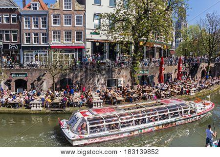 UTRECHT, NETHERLANDS - APRIL 09, 2017: Tourists taking a tour through the canals of Utrecht, Holland