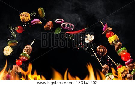 Collage of grilled meat skewers and vegetables on black background