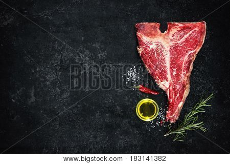 Raw dry aged t-bone steaks for grill with fresh herbs