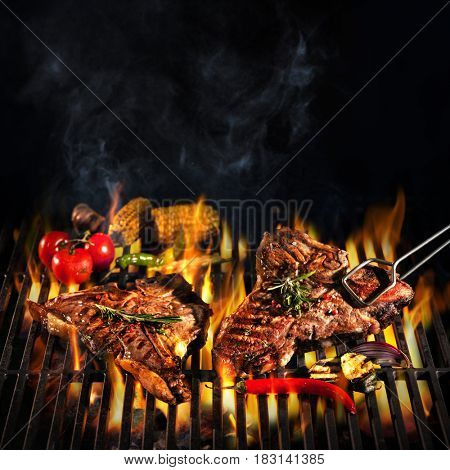 Beef T-bone steaks on the grill with flames