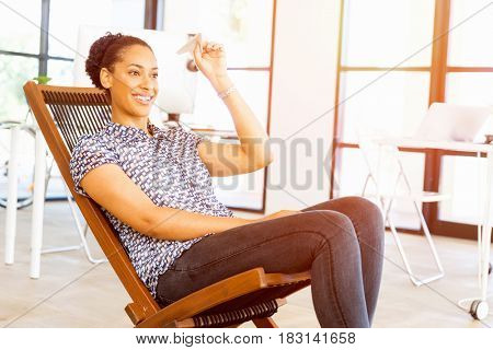 Young woman in office holding paper plane