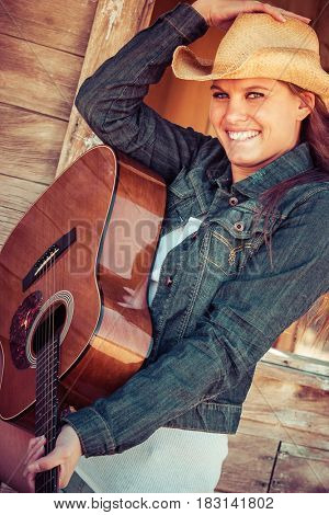 Happy country woman playing guitar