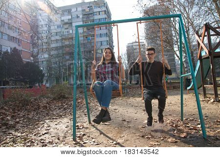 Two happy smiling teenager on the swing