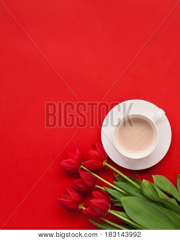 Vertical studio shot of bright red flowers and a coffee cup on the red background.