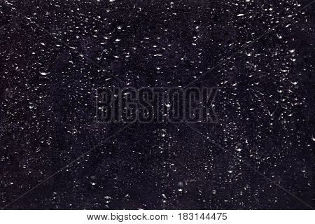 Abstract dark background with old glass texture with water drops