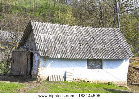Old Wooden Shed With A Wooden Roof In A Sunny Summer Day. Traditional Ukrainian Architecture.