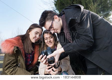Young photographer shows photos on display to the girls