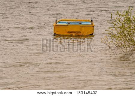 Small yellow wooden boat drifting in lake with choppy water with a lush green bush extending from the shore over the water