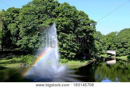 Fountain with a rainbow in Riga river canal that flows through Bastion park (Bastejkalns). Riga, capital of Latvia.