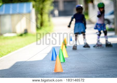 Children Learning To Roller Skate On The Road With Cones.