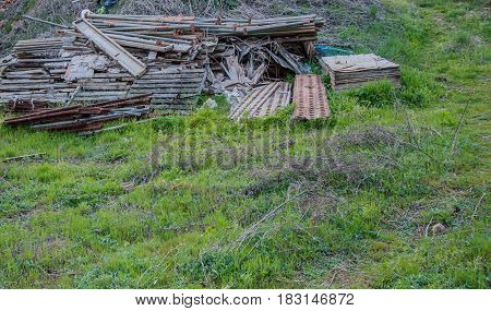 Stack of construction material laying in a field of green grass and dead twigs