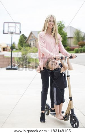 Cute young mother and her little boy playing together on a scooter in the driveway in a suburban neighborhood. Outdoor lifestyle photo of a parent playing with her child