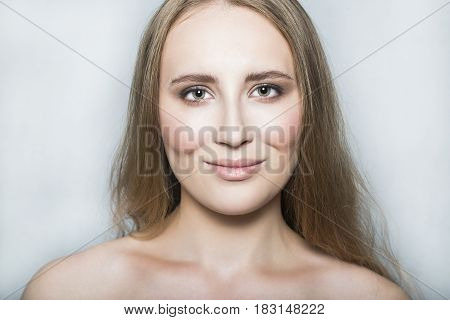 Portrait with face of young blonde beautiful girl with nude make up and long healthy shiny hair with closed eyes, smiling, looking and posing with nude neck and shoulder on white background