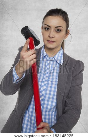 business woman holds a big hammer, pointing with finger