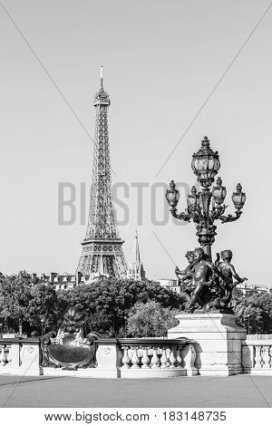 Ornate renaissance street lamp on the famous Pont Alexandre III bridge in central Paris with Eiffel Tower in the distance in black and white. Ronde d'Amours wearing garlands among winged fish. Paris France