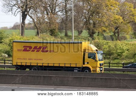 Watford UK - April 24 2017: Yellow DHL lorry in motion on the British motorway M1