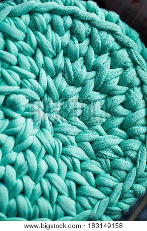 Texture. Turquoise crochet in a circle of knitted yarn fabric.Close