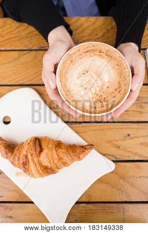Top view on woman's hand holding big cup with cappuccino coffee and fresh French croissant on a wooden table in outdoor cafe. Breakfast with coffee and bread.