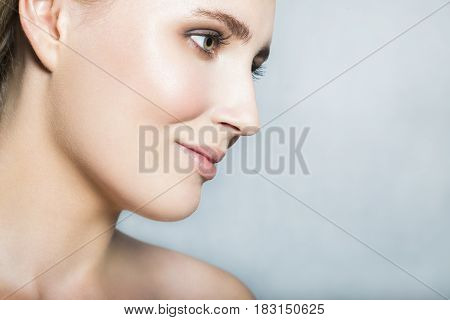Portrait with face of young blonde beautiful girl with nude make up smiling, looking aside and posing with nude neck and shoulder on white background