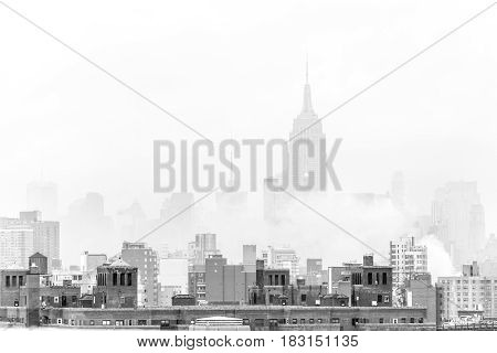 New York City, United States of America - March 24: Misty Manhattan Dimond Reef skyline with Empire State Building and skyscrapers seen from Brooklyn Bridge on March 24, 2015 in black and white.