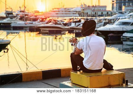 Stylish man and his dog sitting together on pier and enjoying colorful sunset. Man in white t-shirt and black hat. Jack russell terrier puppy on his lap. Luxury yachts docked in sea port.